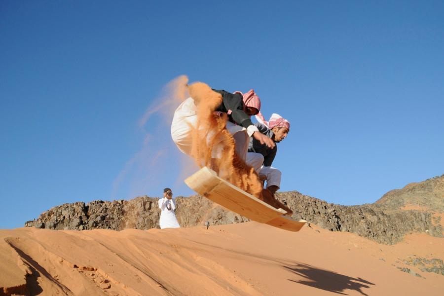 صور رائعة لشبان يمارسون رياضة التزلج على الرمال في صحراء تبوك