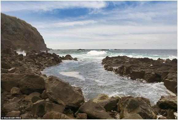 """ينابيع """"Ponta di Ferreira""""، في جزيرة """"ساو ميغيل""""، البرتغالية، والتي تصب في المحيط الأطلسي، وتقع وسط مجموعة من صخور الحمم السود"""