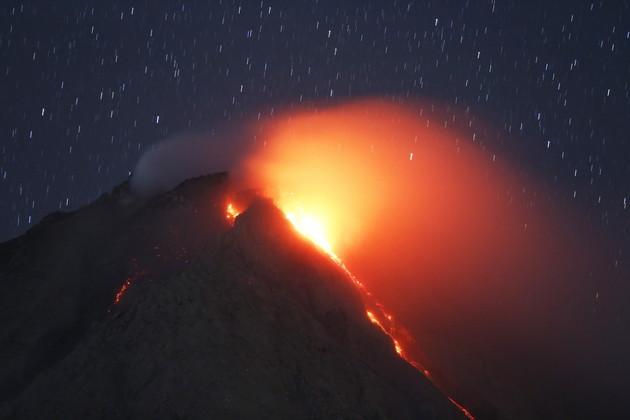 مشاهدة الحمم المنبعثة من بركان جبل سينابونغ من قرية في هضبة كارو شمال سومطرة بإندونيسيا