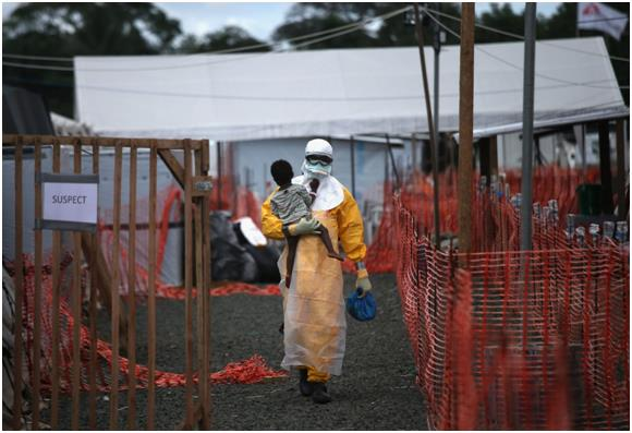 """عامل في منظمة """"أطباء بلا حدود""""، يرتدي ملابس واقية أثناء حمله طفلاً، يشتبه في إصابته بفيروس """"إيبولا""""، وذلك بمركز العلاج في ليبي"""