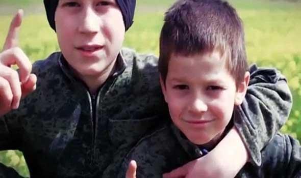 طفلين يقومان بإعدام سجينين سوريين