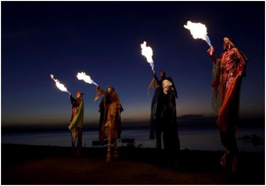 """مشاركون في مهرجان """"Kaisokah Moko Jumbies""""، يقومون بإشعال النيران، بالقرب من قاعدة """"Trinidad """" في مدينة """"سان فرناندو"""" الإسبانية"""
