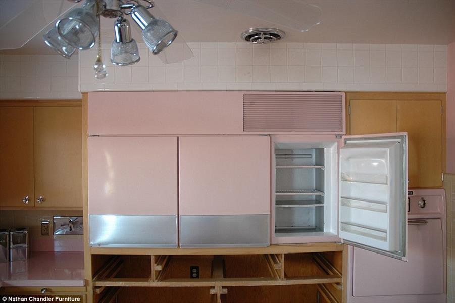 ثلاجة مصممة بشكل عملي وسط مكونات المطبخ، وليسهل على الطاهي الوصول إليه