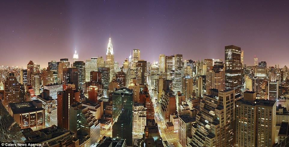 """غابة من الأبنية المضاءة، لقطة بانورامية ساحرة لحي مانهاتن، نيويروك ويبدو مبنى """"امباير ستيت"""" مشعًا في الوسط """
