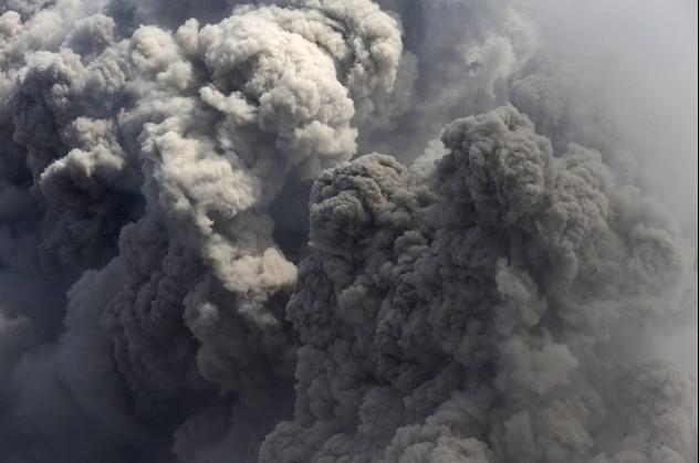 مشاهدة أعمدة الرماد المنبعثة من بركان جبل سينابونغ من إحدى القرى بهضبة كارو شمال سومطرة بإندونيسيا
