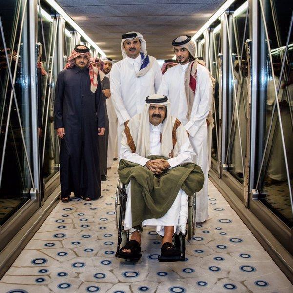 أمير قطر يقود والده على كرسي متحرك لدى عودته من سويسرا
