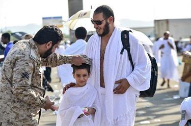 بالصور.. رجل أمن يتخلى عن قبعته لحماية طفل من حرارة الشمس بالمشاعر المقدسة