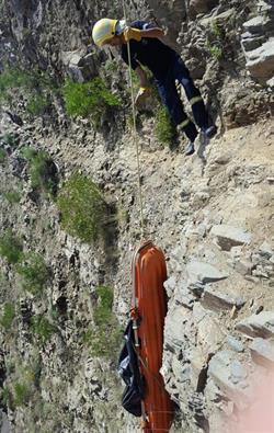 """بالصور.. """"مدني الداير"""" ينتشل جثة مقيم غير نظامي من منحدر جبلي وعر"""