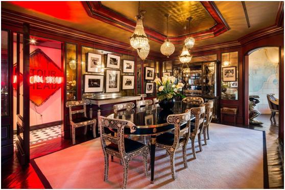 """غرفة الطعام  بجدرانها الذهبية والمضاءة بأضواء """"النيون"""" ."""