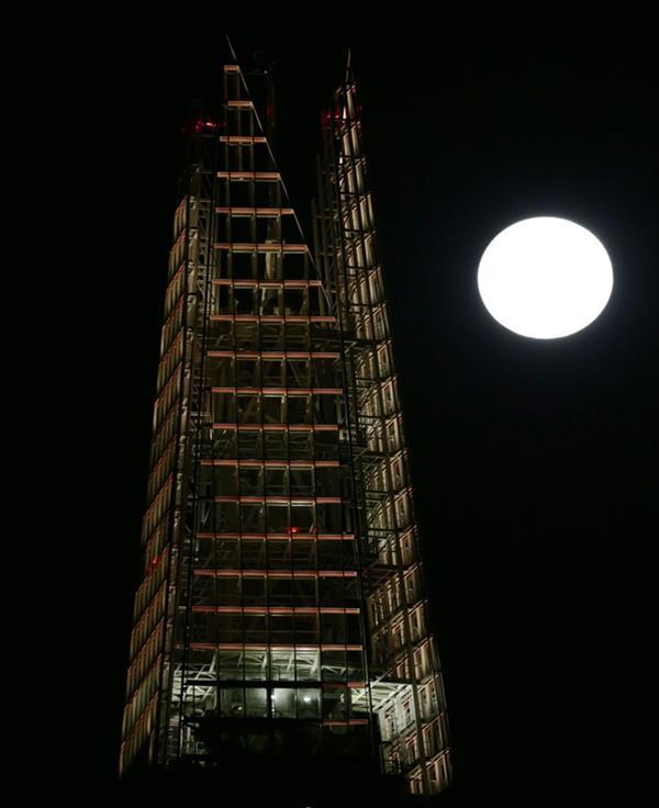 """""""القمر العملاق"""" يظهر خلف ناطحة سحاب """"شارد"""" اللندنية."""