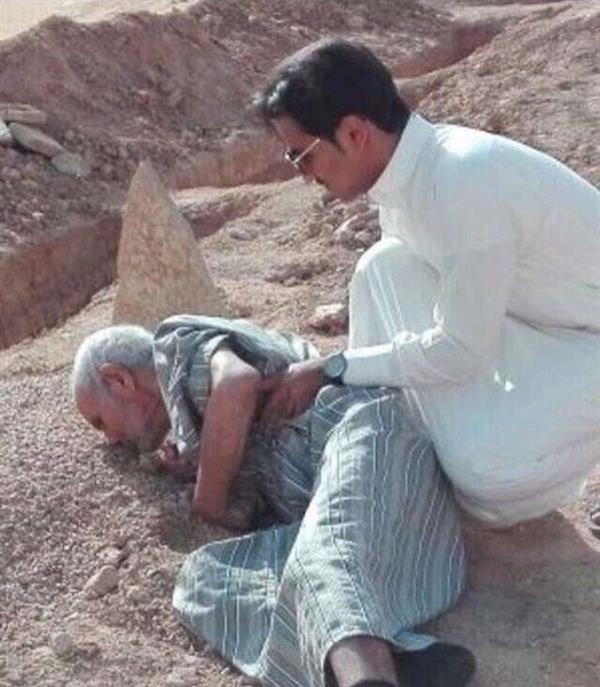 صورة لمواطن مسن ينكب على قبر زوجته ويقبله