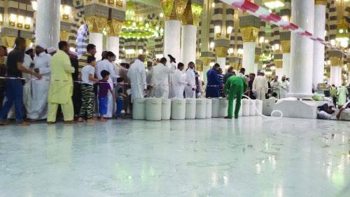 عامل سقيا زمزم داخل المسجد النبوي مرتديا نعليه