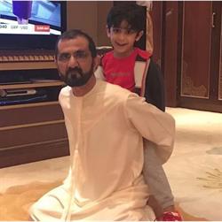 محمد بن راشد وهو يلعب مع طفلين في بيته
