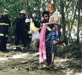 شاهد.. فرد من الدفاع المدني يحمل مسنا بين يديه لينقذه من السيول بجازان