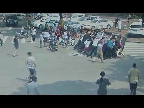 المارة يرفعون سيارة انقلبت بعد اصطدامها بأخرى في الصين