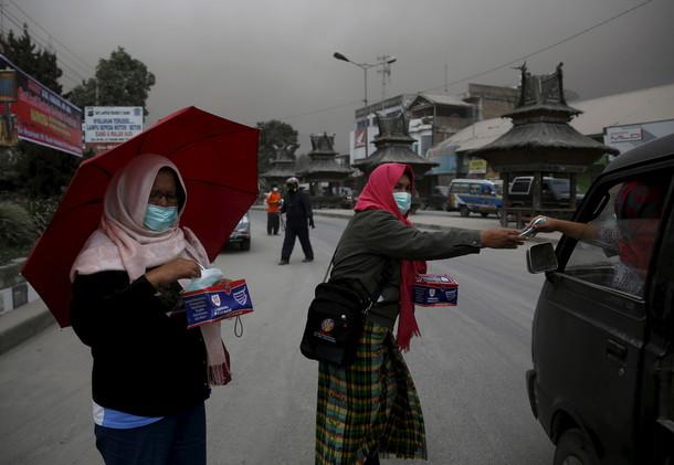 نساء يوزعن أقنعة واقية من الرماد المنبعث من بركان جبل سينابونغ في قرية براستاغي شمال سومطرة
