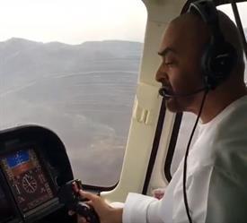 محمد بن زايد يقود مروحية في سماء الإمارات وسط أجواء غائمة (فيديو)