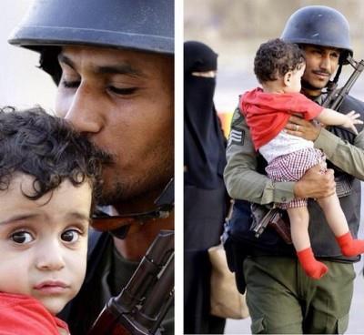 صورة رجل أمن سعودي مع طفل يمني